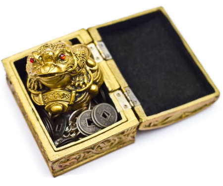 superstitions: Feng Shui frog on chest with coins isolated on white Stock Photo
