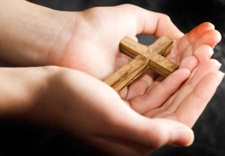 Wooden cross in the hands
