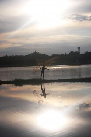 Fishing Man throwing fishing net during sunset at  Ratchaburi Thailand Stock Photo - 19747096