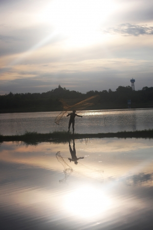 Fishing Man throwing fishing net during sunset at  Ratchaburi Thailand Stock Photo - 19747096