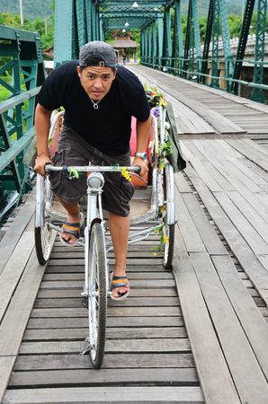 Riding tricycle on Bridge over Pai River at Pai at Mae Hong Son Thailand photo