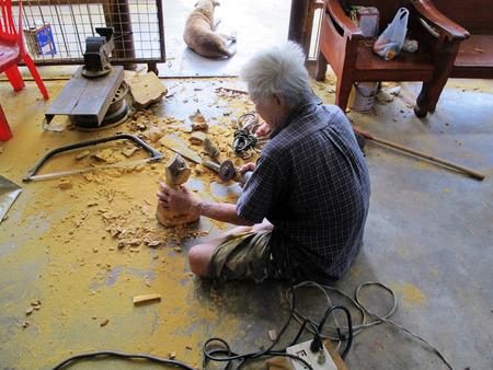 schnitzer: Carver alten Mann schnitzt Holzfigur Buddha bei Thailand