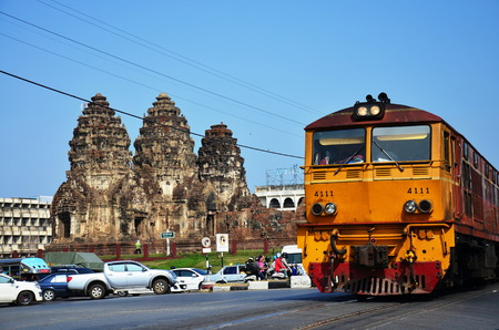 LOPBURI, THAILAND- JANUARY 8   Red orange train on railway near Phra Prang Samyod - Lopburi Thailand on Jannuary 8, 2011 in Ayutthaya, Thailand