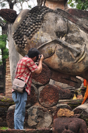 KAMPHAEPHET, THAILAND- JUNE 6   Traveler take a photo Buddha image at Kamphaeng Phet Historical Park Aranyik area,Buddha of thailand on June 6, 2012 in Kamphaengphet Thailand