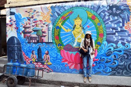 Traveler Thai Women with wall painting on street in Basantapur Durbar Square at Kathmandu Nepal photo