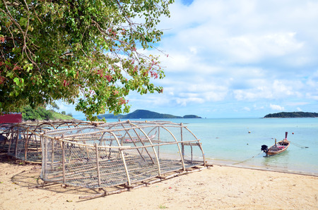 Bamboo fish trap and Fishing Boat at Rawai Beach of Phuket Thailand photo