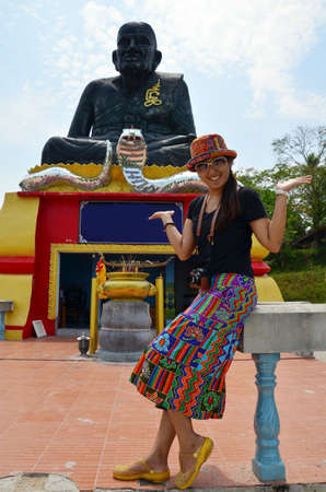 pu: Portrait Thai woman with biggest statue of Luang Pu Thuat in Phatthalung Thailand