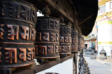 Prayer wheels in Swayambhunath, Nepal   Traditionally, the mantra Om Mani Padme Hum is written in Sanskrit on the outside of the wheel  photo