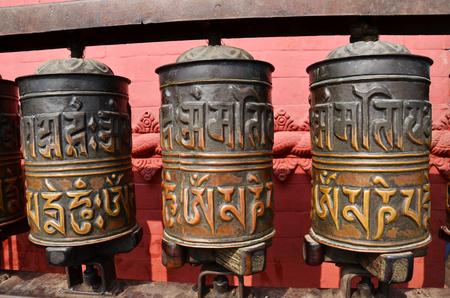sanskrit: Prayer wheels in Swayambhunath, Nepal   Traditionally, the mantra Om Mani Padme Hum is written in Sanskrit on the outside of the wheel  Stock Photo