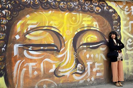 Traveler Thai Women with wall painting on street in Basantapur Durbar Square at Kathmandu Nepal