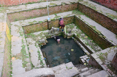 Nepalese women fill water in tank for use and drink at Sacred pond on November 2, 2013 in Patan Nepal