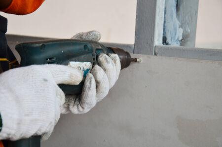 Man use drilling machine drill screw photo