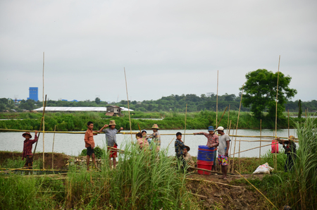 Burmese people fishermen prepare tools for catch fish while raining at fish pond on July 13, 2014 in Bago, Burma.