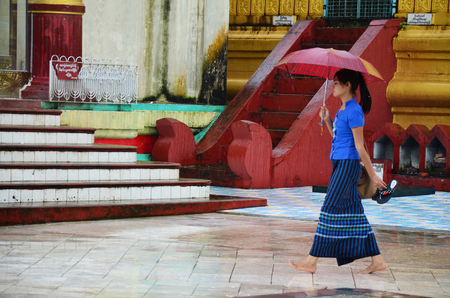 Burmese people walking while raining at Shwemawdaw Paya Pagoda is a stupa on July 13, 2014 in Bago, Burma.
