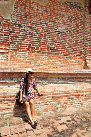 Thai woman portrait at Brick wall Background of Temple in Ayutthaya Thailand. photo
