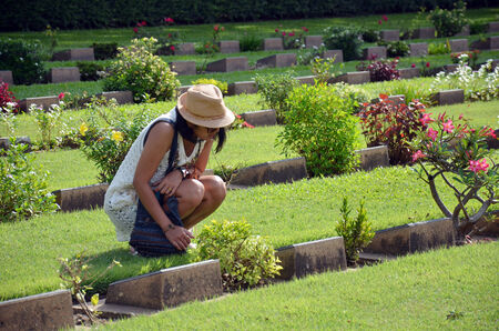 Thai woman reading word on gravestone Kanchanaburi War Cemetery (Don Rak) photo