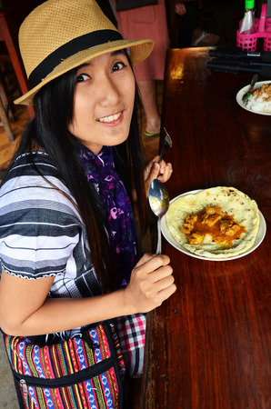 Thai woman eating Roti Mataba with Chicken massaman Curry photo