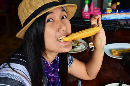 Thai woman eating Rice porridge or Congee with white deep-fried doughstick or sugar sponge cake photo