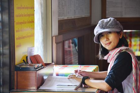 Thai women write memory on book.