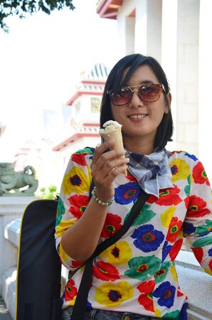 vihara: Thai woman eating Ice cream cone at  Wat Bowonniwet Vihara, or Wat Bowon located on Bangkok Thailand.