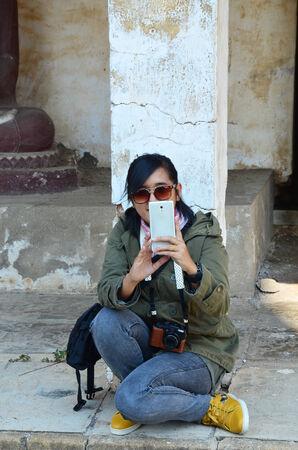 Thai women take photo by mobile phone in Aranyikawas Temple at Ratchaburi Thailand photo