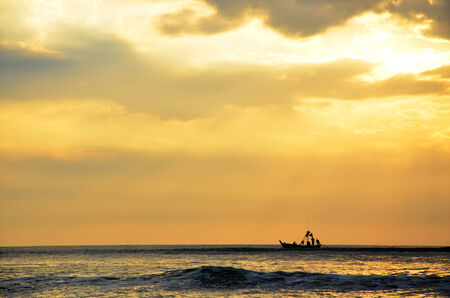 Fishing boat floating on the sea in morning and sunrise time at Hat Chao Samran beach of Phetchaburi Thailand photo