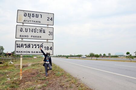 way to go: Thai woman riding chopper motorcycle on the way go to Ayutthaya with guidepost or Distance signs