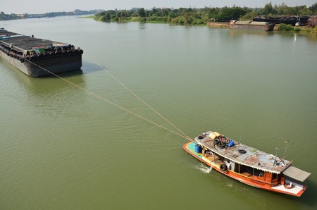 Barge and Tug Boat cargo ship in Choaphraya river at Ayutthaya Thailand photo