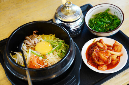 Korean food set Bibimbub with Kimchi and Japanese seaweed salad in a hot stone bowl and side dish photo