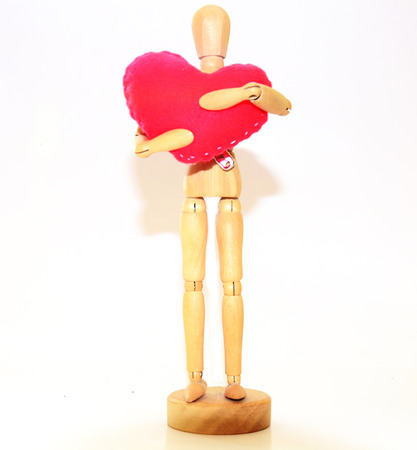 Human wooden figure with Handmade Heart model made from velvet photo
