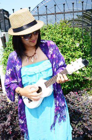 acoustic ukulele: Thai woman play Ukulele or small Acoustic Guitar in garden