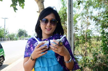 comiendo helado: Mujer tailandesa que come el helado