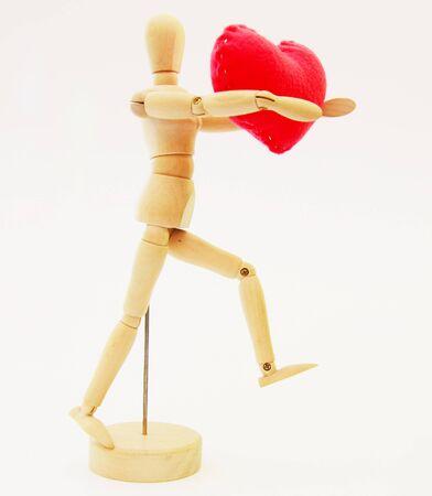 Human wooden figure with Handmade Heart model made from velvet photo