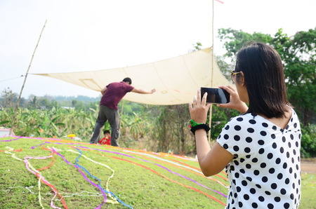 przodek: Thai women use mobile phone take photo Ceremony of Ancestor Worshipping and Sacrificial offering in Qingming Festival at Ratchaburi, Thailand.