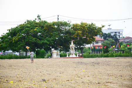 Children playing kite with family at space lands front of village in Nonthaburi, Thailand photo