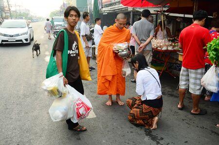 limosna: La gente pone ofrendas de comida en un recipiente limosnas budista en Bangyai peque�o mercado el 12 de abril de 2015, de Nonthaburi Tailandia.