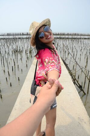 Thai woman lead someone by the hand and hold on the walkway bridge in Mangrove forest or Intertidal forest at Bangkhunthein in Bangkok Thailand. photo