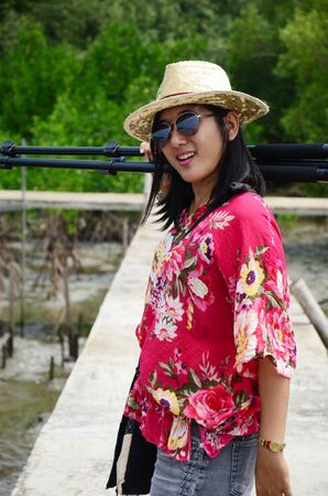 Thai woman portrait with tripod on the bridge in Mangrove forest or Intertidal forest at Bangkhunthein in Bangkok Thailand. photo