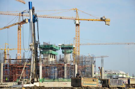 Builder worker in safety protective equipment with Machinery Building Construction Site at Bangkok Thailand photo