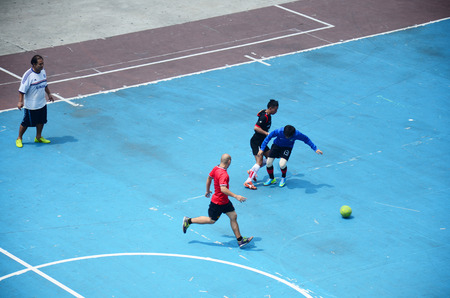 Thai men playing football or soccer on field at front of sport stadium on April 5, 2015 in Bangkok Thailand