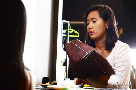 Thai woman sewing Handmade Bag Leather in workshop