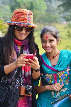 Traveler Thai women take photo with nepalese girl at International Mountain Museum on October 31, 2013 in pokhara of Annapurna Valley Nepal
