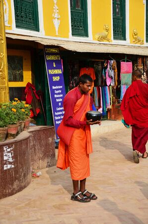Nepalese monk standing at Boudhanath temple for receive donation from people on October 29, 2013 in Kathmandu Nepal