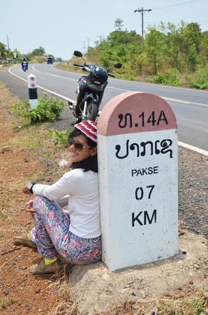 milestone: Thai woman portrait with Milestone go to DONTALAD at Pakse in Champasak Laos Stock Photo
