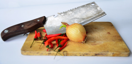 Chili and onion with kitchen tools on white background photo