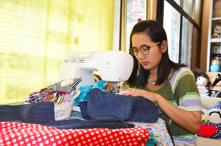 Asian women use machine sewing clothes