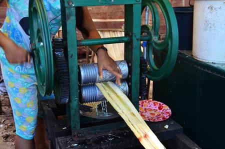 machine made: Burmese girl made sugar cane juice by maker manual machine for sale traveler Stock Photo