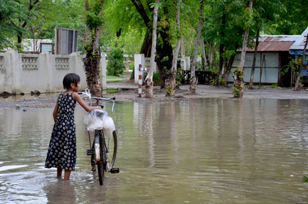flood area: Burmese girl riding bicycle in flood area after raining at village between go to Mandalay Palace on May 19. 2015 in Mandalay, Myanmar.