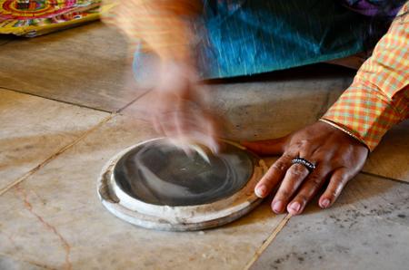 thanaka: Burmese woman made powder thanaka from ground bark Stock Photo