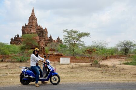 pagan: Traveler thai woman ride motorcycle travel around Ancient City in Bagan (Pagan) Archaeological Zone, Myanmar with over 2000 Pagodas and Temples.